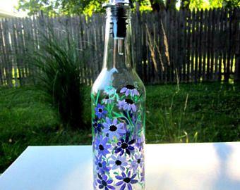 Luz verde botella de vino reciclada en un dispensador de jabón de plato de brillante, divertida, alegre. Pintado a mano con tonos de flores púrpura y plata. En la pintura de cristal por lo que es bien a mano lavar cuando sea necesario. Diluir el jabón así que durará más tiempo. Vertedor fácil. También viene con una mano de ganchillo (por mí) trapo de plato. Ideal para su cocina o hace un maravilloso regalo único. Reciclar siempre es genial