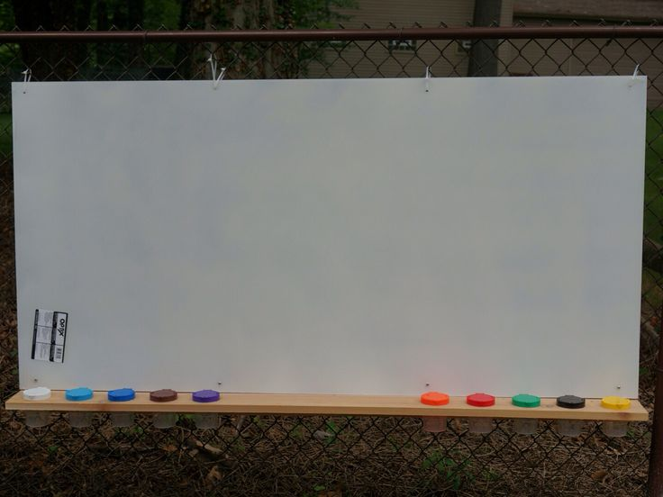 Kids outdoor paint station/easel. A sheet of plexiglass sprayed white on the back. 4X6 piece of cedar to hold the paint cups bought from Lakeshore. We zip tied it to the chain link fence. Children can paint, wash and repeat!