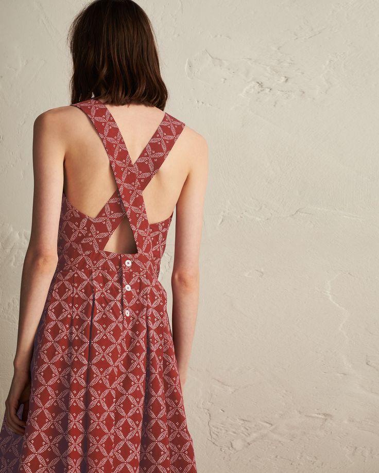Crisp, discharge printed cotton poplin. Cross back with button opening below. Deep waistband with pleats below. Pockets.