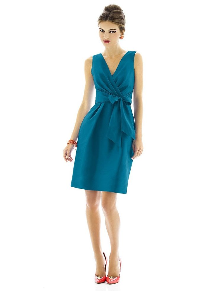 Peau de soie enwraps the slim A-line silhouette of Dessy Alfred Sung D597 bridesmaid dress, tied around the natural waist with an off-center bow sash. Pleated panels sculpt the surplice bodice, which defines the V-neckline. Beneath, the slightly pleated skirt flows into an above-the-knee length complete with side pockets.