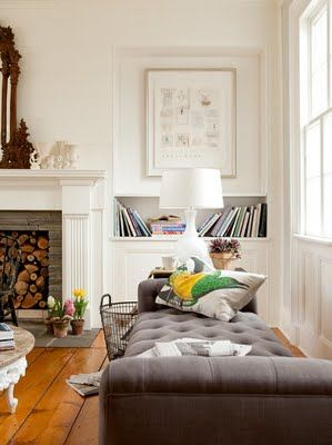 built-in shelf and fireplace with upholstered grey ottoman