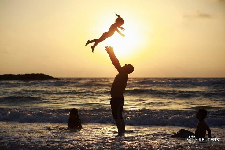 A Muslim man plays with his daughter along the shore of the Mediterranean Sea during the Muslim holiday of Eid al-Fitr, in Ashkelon, Israel June 26, 2017. REUTERS/Amir Cohen #reuters #reutersphotos #eid #israel #childhood #beach #sunset
