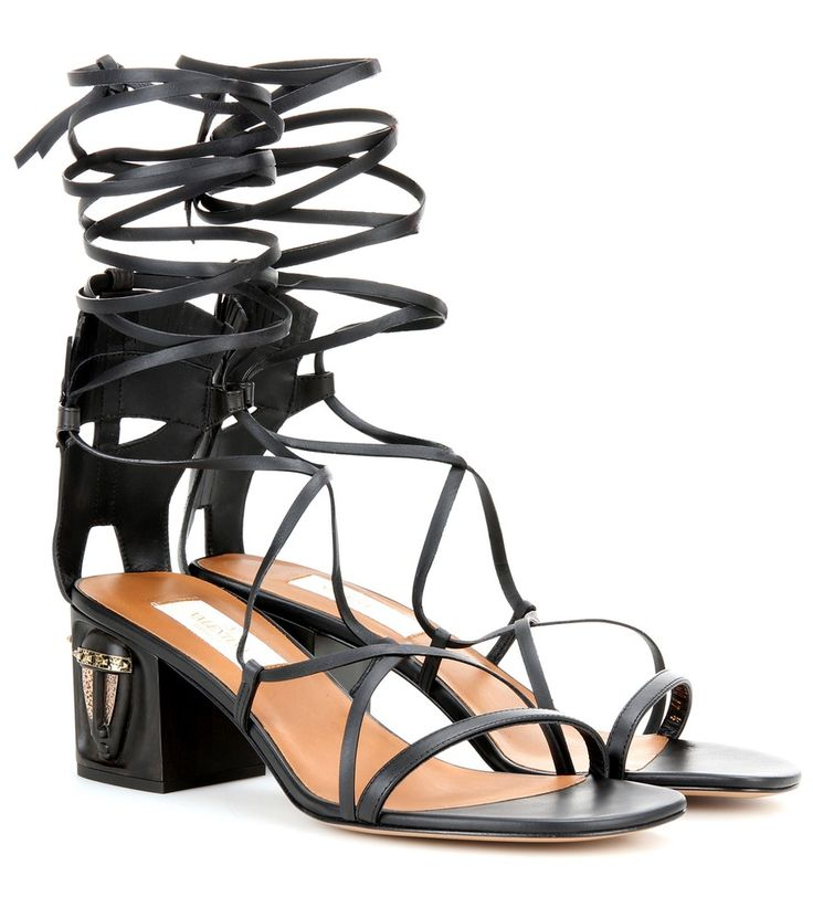 Valentino - Embellished leather sandals - Valentino was inspired by Africa this season, and the look is shown best on these tribal mask-inspired sandals. Made from thin strips of black leather, this lace-up pair features cut-outs to the heel to create a subtle tribal masks that matches the ones engraved in the wooden heel. Let the strappy look standout with short hemlines. seen @ www.mytheresa.com