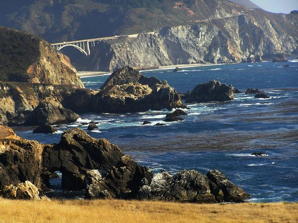 Road Trip: California's Pacific Coast Highway  The route starts in historic Monterey, visits the art colony of Carmel, and threads through Big Sur, where mountains plunge into the Pacific. Farther south, the landscape mellows to oak-studded hills as the road passes Hearst Castle on its way to Morro Bay. In places, the road has narrow shoulders and sharp drop-offs, so stay alert.