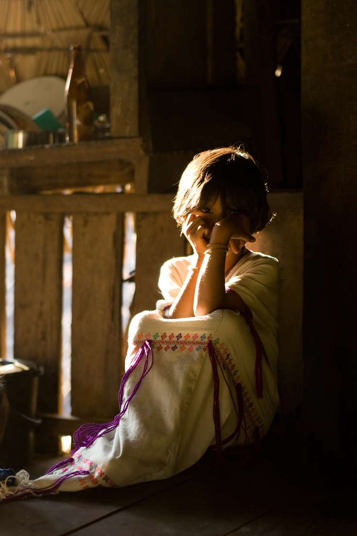 a Karen girl sitting in her house. this photo had been taken at her small village near Mae La refugee camp, border of Myanmar.
