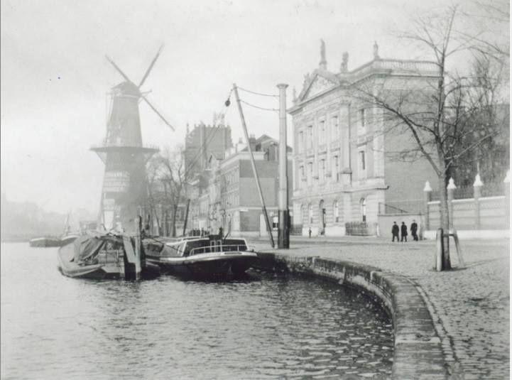 Kijk op de Coolvest en de Coolsingel met korenmolen De Hoop tussen 1898-1902. Rechts staat het Erasmiaans Gymnasium. De molen staat op de plek waar je nu een rij winkels met onder andere Dakasport en Intertoys vindt. De foto is ongeveer ter hoogte van het Schielandhuis genomen.