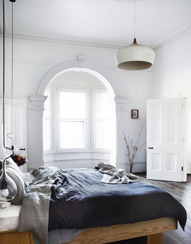 Cozy Swedish inspired bedroom with high ceilings, a platform bed, a simple pendant light, and gray linen sheets
