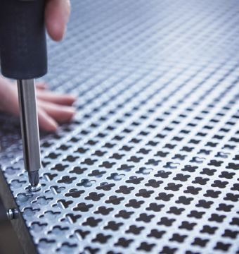A close-up image of a mesh metal sheet being screwed to the back of a IKEA HYLLIS shelving unit.