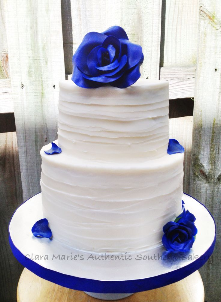 Textured buttercream cake with royal blue roses and petals.