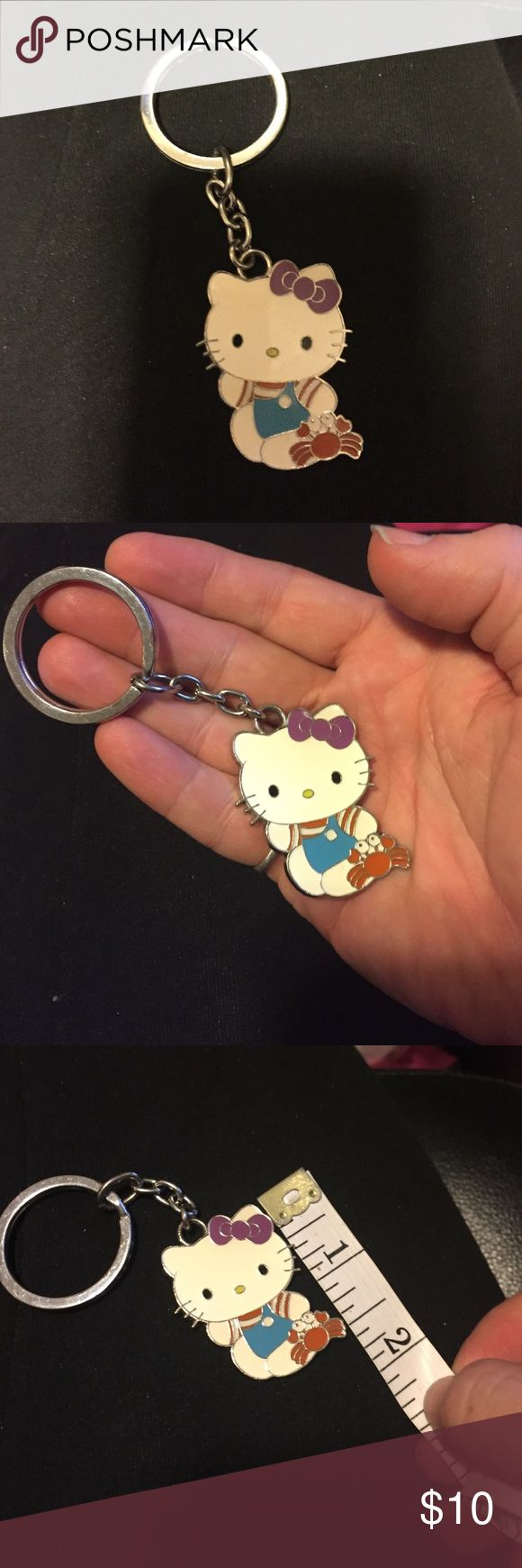 """Hello kitty keychain blue overalls holding a crab Hello kitty keychain- made in France - I thought this was coach but I could be wrong - hello kitty is wearing blue overall and holding a crab measures about an 1 1/2"""" - this is lightly used - has some scratches on back but the front is perfect- save $ on shipping and on items by bundling Hello Kitty Accessories Key & Card Holders"""