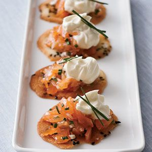 Thomas Keller's salmon cornets (tuiles shaped into tiny cones and topped with creme fraiche and fresh salmon) are a famous kickoff to his luxe and whimsical meals. The original recipe appears in The French Laundry Cookbook (Artisan). Shaping the tuiles into cones is tricky and involves working very quickly with a cornet mold. Instead, leave the tuiles flat, like crackers. Top them with store-bought smoked salmon and creme fraiche.
