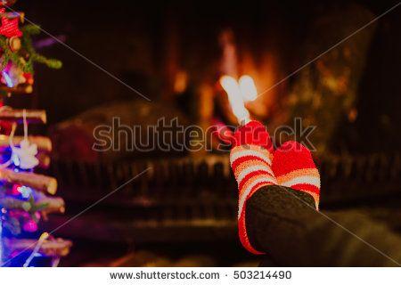 Woman feet in wool socks warming by fireplace