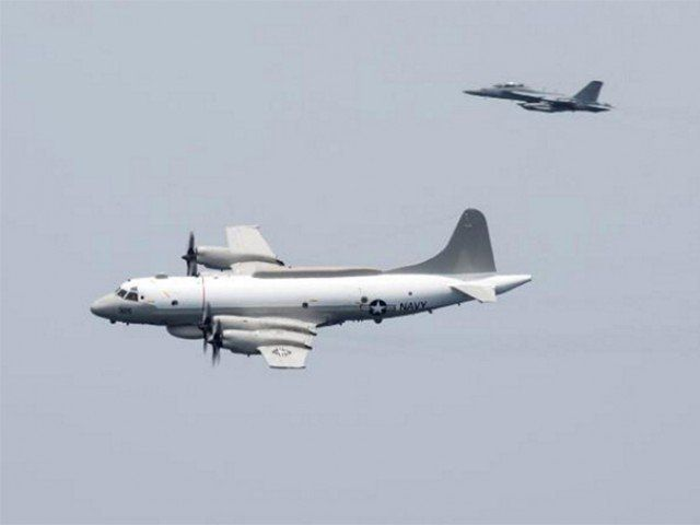 A US Navy EP-3E Aries signals reconnaissance aircraft, escorted by an EA-18G Growler electronic warfare aircraft, performs a flyby over aircraft carrier USS Harry S. Truman in the Arabian Gulf April 24, 2016. PHOTO: REUTERS/FILE