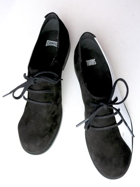 The Camper Twins Oxford does double duty serving as both a black shoe and a white shoe-- and maybe a black-and-white shoe, if that's what you need. Plus, in fine Camper tradition, they are super super comfortable.Leather upper with rubber outsole.Order in whole European sizes.
