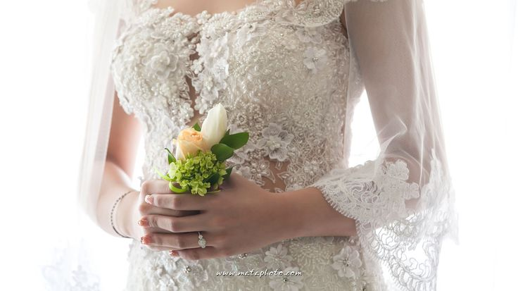 Hand bouquet, wedding ring, and wedding gown detail