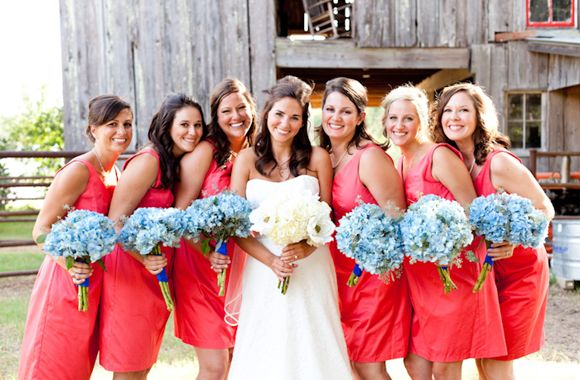 Bright coral bridemaids dresses and blue bouquets.
