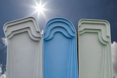 Three fiberglass swimming pool shells standing up on one end