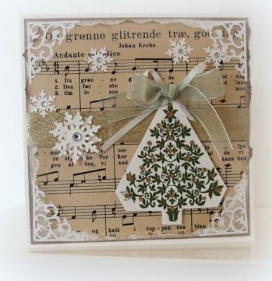 Christmas carols from old music sheet in back ground. Tree is embossed. Moski