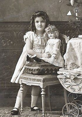 Vintage photo of young girl with her doll, circa 1910 - 1925.