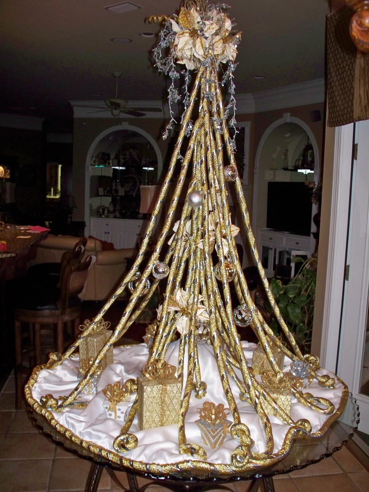 Designer Christmas Tree for Cathedral Square gallery. Made from 25 cover ropes attached to a 4' wooden closet rod.  Skirt made from same material and off white satin.  Ropes were tied in knot at ends and top was made from wires and silk flowers. Gifts under tree are gold and silver, ornaments are from Razz.