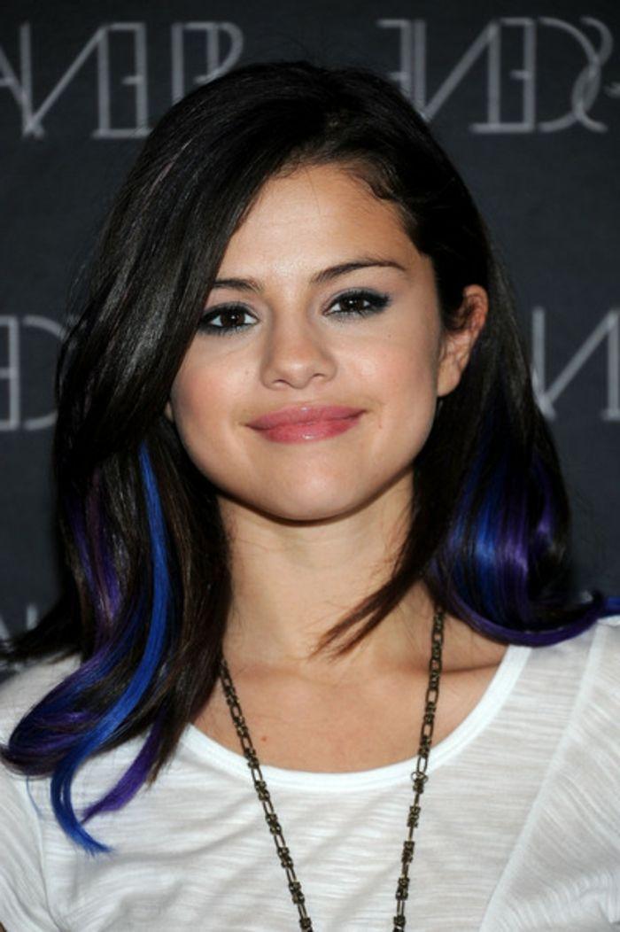 Selena Gomez, schwarze Haare mit dunkelblauen Strähnen, natürlicher Make up, weiße Bluse, lange Kette