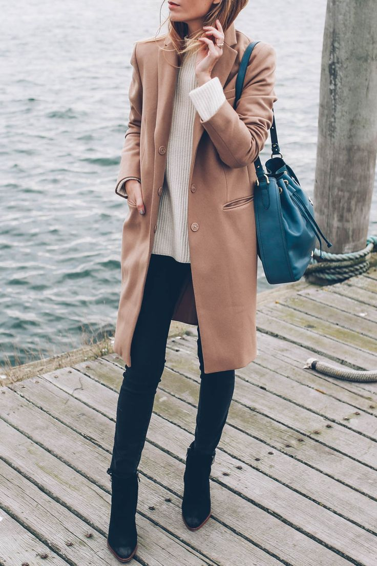 Jess Kirby wears black skinny jeans with ankle boots and a camel wool coat
