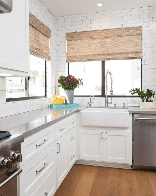 Mochen sleek white kitchen with shaker style cabinet doors, gray quartz countertop and counter-to-ceiling subway tile.