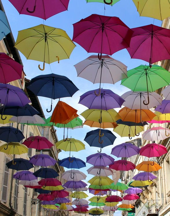 The image of summer 2015: The image of the month - A superb colorful and poetic cliché these floating umbrellas suspended from cables in the street, in Toulouse. If you search out the anti social peoples' corner (i;e. the smokers' area after entry into flight waiting area in Roissy/Charles de Gaulle Airport in Paris (not so easy to find) the ceiling is decorated similar. ©  Claude Gortchakoff