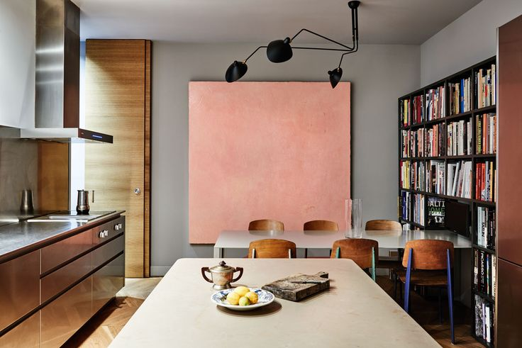 Stainless steel kitchen, Serge Moule wall light and Jean Prouve dining chairs  by Vitra , art in kitchen