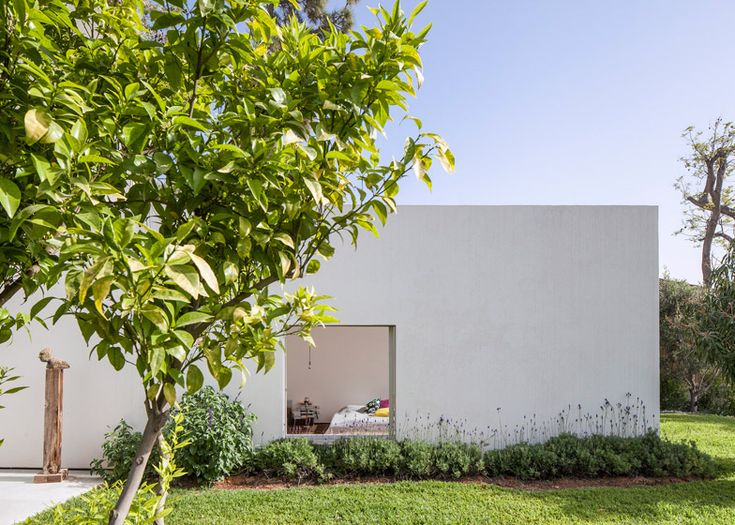 The three parallel boxes that form this house in Tel Aviv all culminate in a full-height glazed wall facing the garden