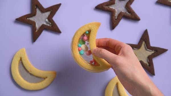 Recipe with video instructions: These beautiful, buttery shortbread and chocolate cookies will take you over the moon. Ingredients: Chocolate Star Cookies, 1 cup unsalted butter, softened, 1 cup sugar, 1 large egg, 1 ½ tsp vanilla, 2 cups all-purpose flour, ¾ cup cocoa powder, ½ tsp salt, Vanilla Moon Cookies, ½ cup + 1 Tbsp butter, softened, ½ cup granulated sugar, 1 large egg, 1 ½ tsp vanilla extract, ½ tsp almond extract, 1 ½ cups all-purpose flour, Candy Glass, ¼ cup light corn syrup, ½…