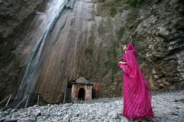 Μια πιστή κοιτάζει τον καταρράκτη που βρίσκεται κοντά στο ναό Baba Dhansal στις Ινδίες.