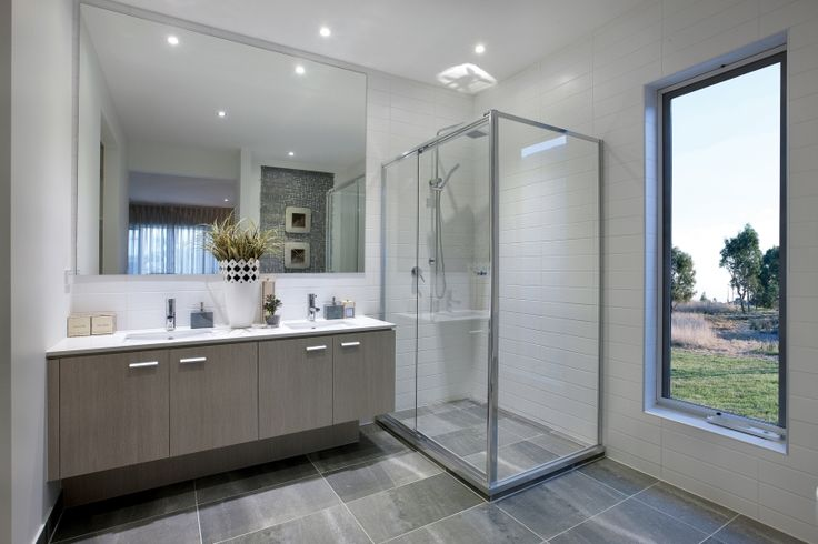 Perfectly simple this stunning main bathroom uses earthy tones in soft brown cabinetry,large grey scale floor tiles and white subway wall tiling.