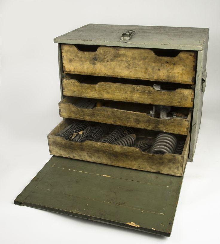 Verktygslåda av trä med bärhandtag på kortsidorna, handtag ochbeslag är gjorda i metall. inuti lådan är det 4 utdragslådor varav alla har innehåll förutom det översta. Innehållet består av 15 st fjädrar samt 11 st verktyg, flertalet verktyg är av nyckelmodell. I lådan liger även 2 st låsnycklar troligtvis till ett hänglås.