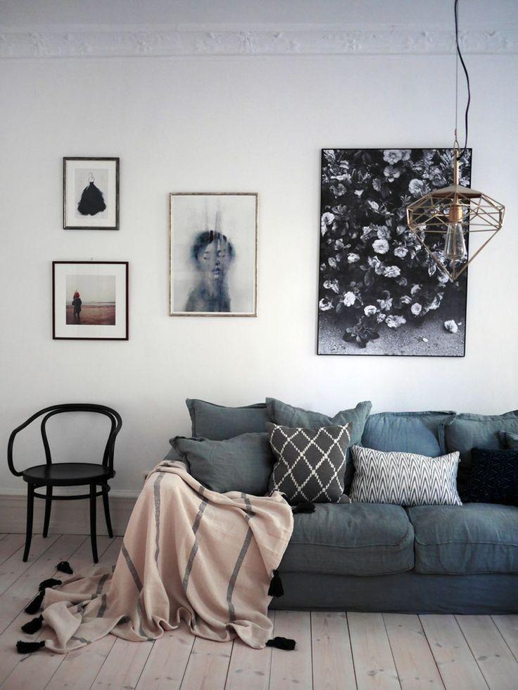 canapé gris foncé rembourré décoré de coussins gris et d'une couverture rose