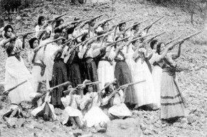 """Durante a Revolução Mexicana, as combatentes femininas conhecidas como soldaderas entram em combate ao lado dos homens, apesar de elas frequentemente enfrentarem abusos. Uma das mais conhecidas das soldaderas foi Petra Herrera, que se disfarçou de homem e passou a se chamar """"Pedro Herrera"""". Como Pedro, ela estabeleceu sua reputação ao demonstrar liderança exemplar."""