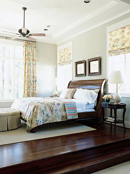 Center Stage ~ This multilevel master bedroom is stately and refined. The light gray walls beautifully complement the yellow floral textiles, and the towering windows add plenty of light and drama.