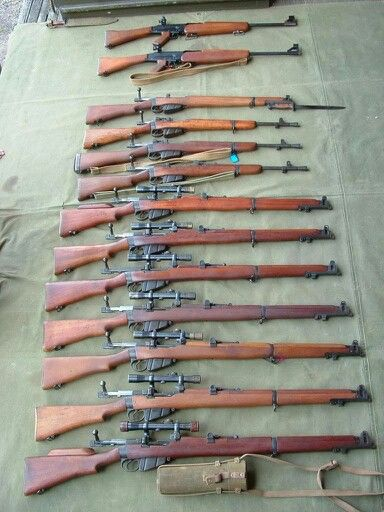 Largely Lee-Enfield rifles (not sure what the two are at the top).  Three No.5 Mk Is, seven No.1 / SMLEs all with telescopic sights and what appears to be a shortened SMLE with bayonet at the top.