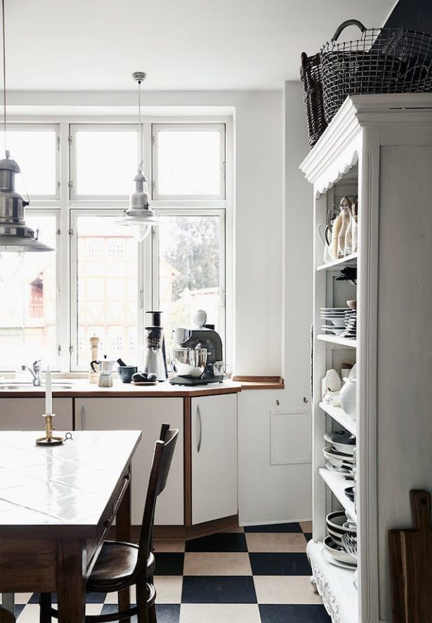 Home Design White Kitchen Interior With Black And White Checkered Floor Tiles Alongside Natural Wood Table And White Varnished Open Cupboard Near White Framed Windows Stylish Home In Contrasting Colors And With A Personality
