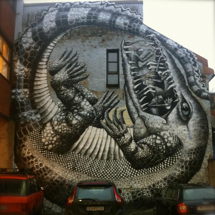 Denne fabelkrokodillen = fet. Rett og slett. Pryder parkeringsveggen til venstre inngang Brenneriveien 11. Det er noe  mytologisk over det hele. Måten krokodillen ligger sammenkrøket med tannsamlerne som befester kjeften. #Streetart #crocodile #mythology