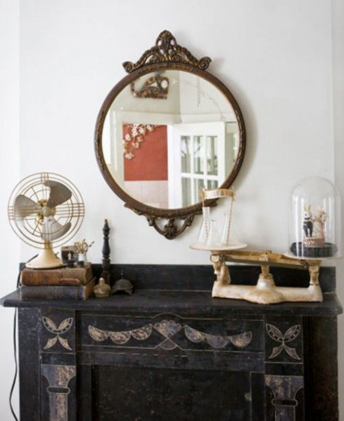 8. Go round. Juxtapose round mirrors or artwork with the rectilinear mirror shape of a fireplace. This mantel carries the round theme from the mirror through to the objects – the circular shape of the fan and the oval bell jars (that protect the couple's wedding cake topper)