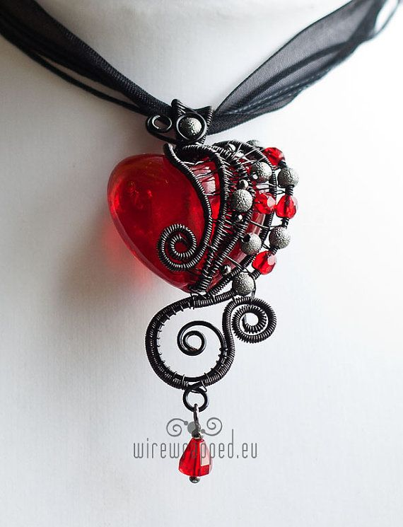 The main bead is a huge red silver foil heart. The wire is enamel plated copper. The other beads are iron and fire polished glass. Measures about