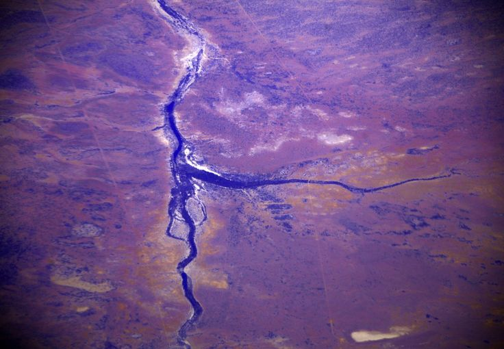 A dried-up river looks like a crack through the Pilbara region. The area supplies nearly 45% of global trade in iron ore.