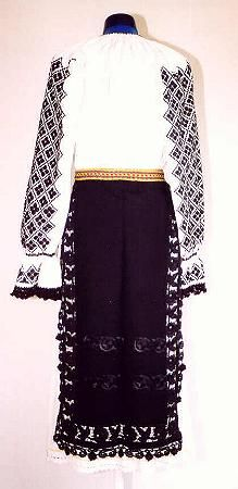 Romanian Women's costume from county of Făgăraş  Black front and back aprons (catrinţe) made of a single width of black felted material. They have two rows of embroidery in black silk on the lower part, and an edging in black openwork with a row of crochet black lace on the sides and the front apron has a fringe made of black silk thread on the hem. White linen underskirt (poale) Narrow fabric belt (brâu) woven with strips of red and yellow.