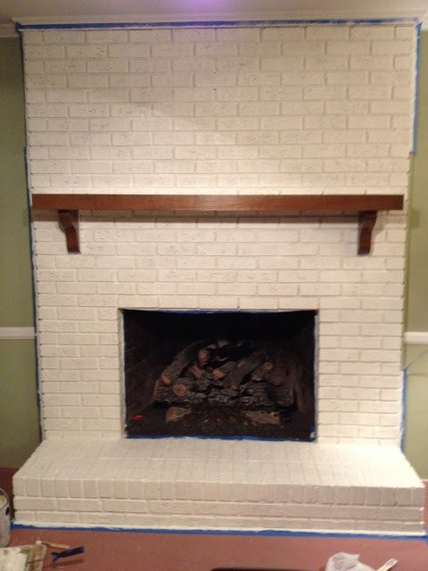 Painted brick fireplace. Natural wood mantle, white brick.