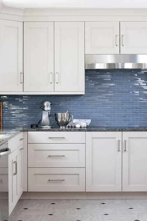 White and blue kitchen features white cabinets adorned with satin nickel pulls paired with black ...