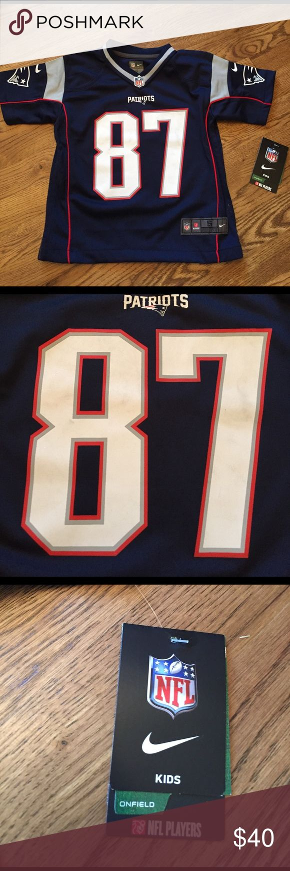 NWT NFL Patriots Gronkowski Jersey Brand new with tags.  Gronkowski jersey 87.  The numbers on front have the faintest staining but it's barely noticeable see pic otherwise excellent condition. Shirts & Tops