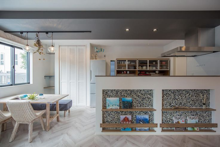 キッチンの腰壁には、ご夫婦お気に入りの海の本を飾るマガジンラックを。下がり天井のグレーのクロスとラック内のモザイクタイルで、全体の雰囲気を引き締めています。