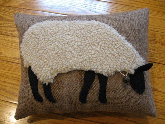 Magnifiques et réalistes pâturage des moutons faites dun tissu laineux en peluche. Il a des jambes en feutre de laine noir, le visage et loreille qui colle cassé loreiller. Jai ajouté une cloche rouillée autour de son cou sur un morceau de ficelle vieilli rustique. Le design est cousu sur un fond de laine marron clair.  Cest ma propre conception et est dessiné, découpé et cousu à la main. Cest un autre de plusieurs oreillers de moutons différents que je fais. Il mesure 9 x 12 et est…