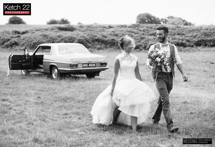 Bride and groom walking from vintage wedding car at Hay on Wye,Herefordshire
